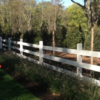 White rail fence with deer fence behind it